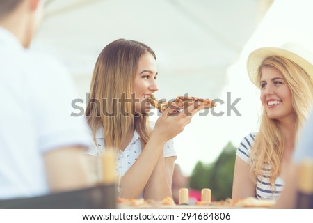 Pretty young girl eating slice of pizza with her friends in the restaurant - stock photo