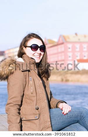 Pretty young girl enjoying beautiful nature near by river during lovely spring weather; outdoor