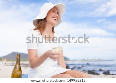 Pretty young girl enjoying glass of wine on the beach - stock photo