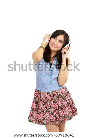 Pretty young girl enjoys listening music. Isolated white background - stock photo