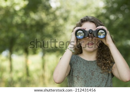 Pretty young girl exploring the environment with a binocular