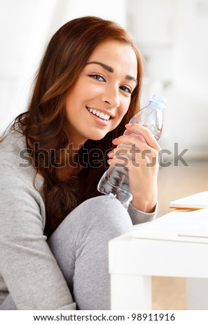 Pretty young girl holding a bottle of water and smiling