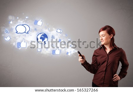 Pretty young girl holding a phone with social media icons in abstract cloud - stock photo