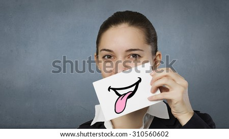 Pretty young girl holding white card with drawn smile showing tongue