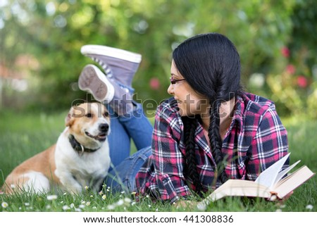 Pretty young girl in happy moment with her dog in grass in park - stock photo