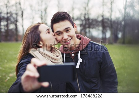Pretty young girl kissing her boyfriend on cheeks while taking self portrait with a mobile phone. Mixed race couple in park. - stock photo