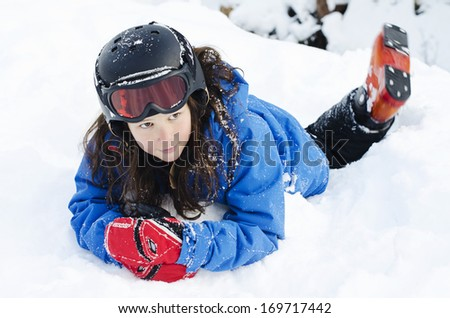 Pretty young girl laying in the snow wearing a ski helmet