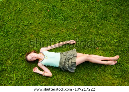 Pretty young girl lying down on grass in the park - stock photo