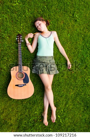 Pretty young girl lying down on grass in the park with her guitar - stock photo