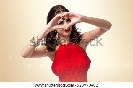 Pretty young girl making a heart with her hands on ocher background