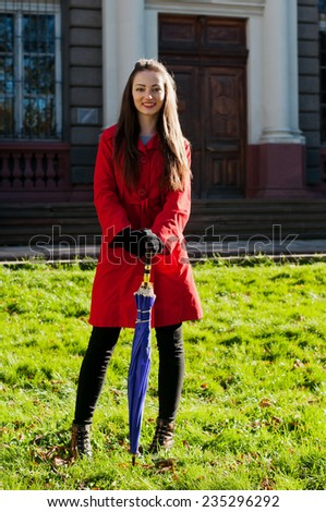 Pretty young girl outdoor stands with umbrella on green grass and looking at camera - stock photo