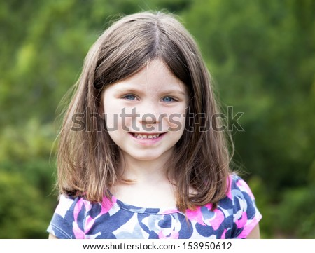 Pretty young girl portrait smiling outdoors - stock photo