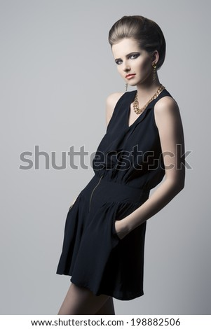 pretty young girl posing with elegant fashion style with cute hair-style and make-up, black dress and golden jewellery - stock photo