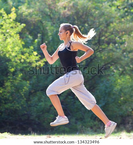 Pretty young girl running in the park - stock photo