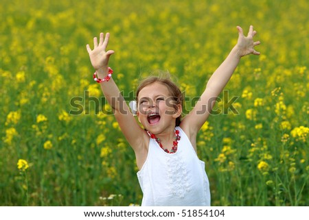 Pretty young girl screaming with delight surrounded by rapeseed flowers