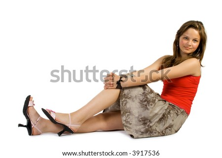 Pretty young girl sets upon floor. Isolate on white.