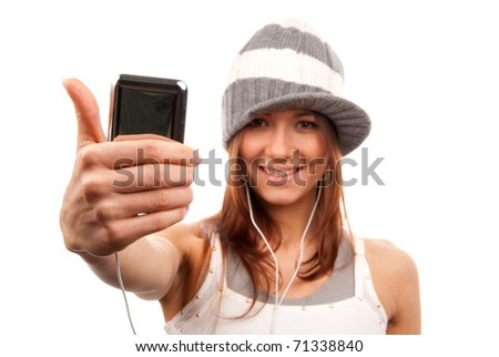 Pretty young girl showing cellular mobile phone and thumb up finger smiling in headphones and hat isolated on a white background. Focus on cellphone - stock photo