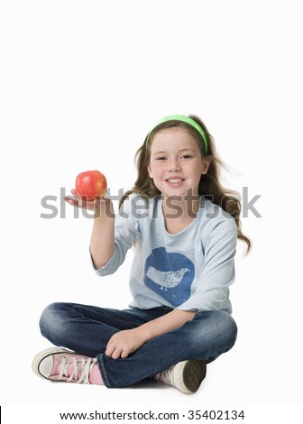 Pretty, young girl sitting cross-legged holding red apple
