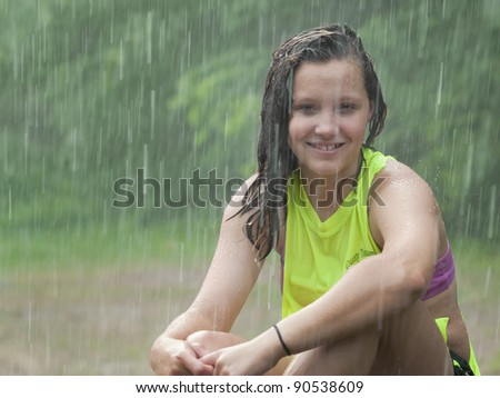 Pretty young girl sitting in the summer rain - stock photo