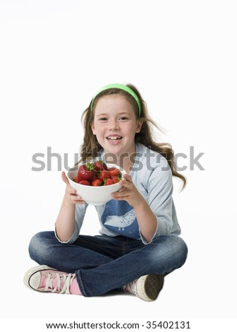 Pretty, young girl sitting on floor holding bowl of strawberries - stock photo
