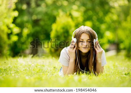 Pretty young girl smiling with pleasure as she listens to music with her eyes closed in bliss while lying on her stomach on the grass in a green lush garden enjoying the spring sunshine - stock photo