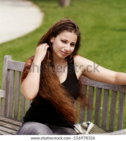 pretty young girl sunbathing on a bench