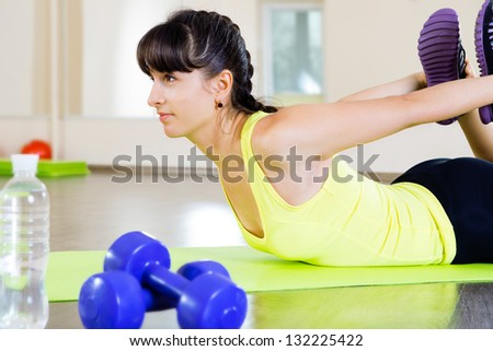Pretty young girl swing back muscles in gym - stock photo