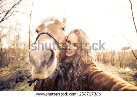 Pretty young girl taking a funny selfie with a hilarious horse - stock photo