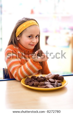 Pretty young girl taking a peace of chocolate from tray - stock photo