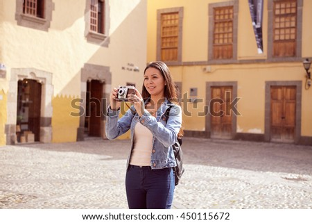 Pretty young girl taking touristy pictures while smiling a toothy smile and her hair loose wearing casual clothing with old buildings behind her