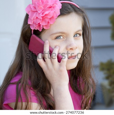 Pretty young girl talking on telephone outdoors. - stock photo