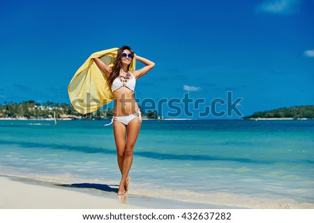 Pretty young girl walking on the beach - stock photo