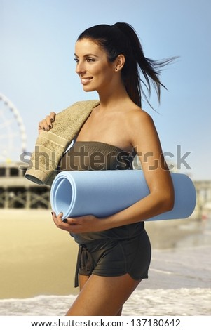 Pretty young girl walking on the beach with beach mattress and towel, smiling happy. - stock photo