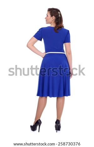 pretty young girl wearing blue dress with the white belt, back view - stock photo