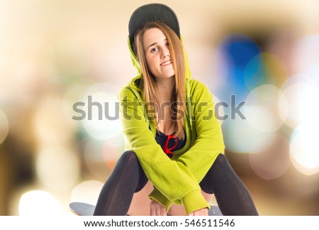 Pretty young girl wearing urban style with skateboard on unfocused background