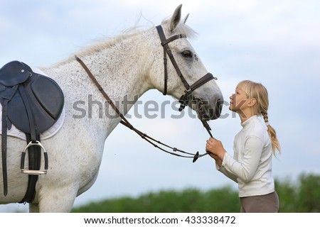 Pretty young girl with a white horse. - stock photo
