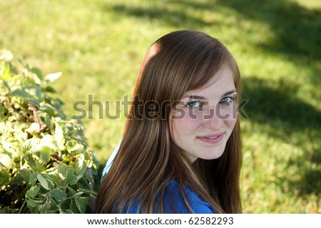 pretty young girl with freckles outside - stock photo