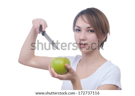 Pretty young girl with green apple and knife - stock photo