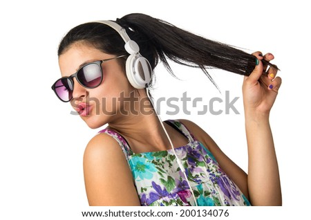 Pretty young girl with headphones and sunglasses dancing and holding her hair - stock photo