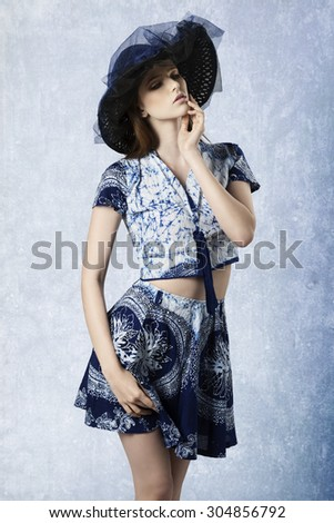 pretty young girl with lovely summer outfit and hat in elegant pose, wearing short skirt and top.  - stock photo