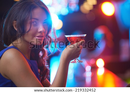 Pretty young girl with martini looking at camera in the bar - stock photo