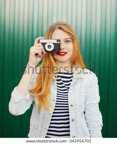 Pretty young girl with retro vintage camera in city over green background - stock photo