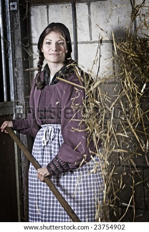 Pretty young girl working in the stable tossing the hay - stock photo