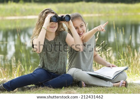 Pretty young girls exploring the environment with a binocular  - stock photo