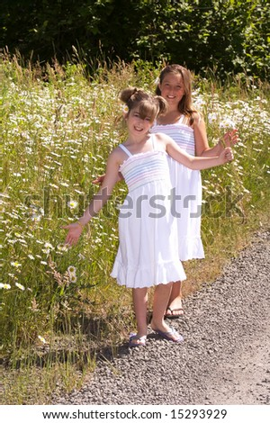 Pretty young girls picking daisies - stock photo