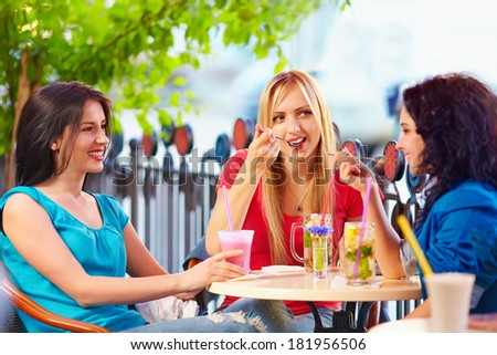 pretty young girls sitting in summer cafe - stock photo