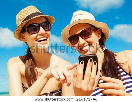 Pretty young girls using smart phone mobile on the beach - stock photo