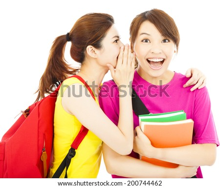 pretty young girls whisper gossip to her classmate - stock photo