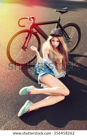 Pretty young hipster blonde girl posing outdoor on the street with sport fixed gear bicycle colorful picture  - stock photo