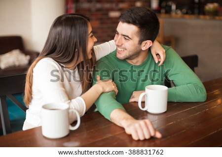 Pretty young Hispanic couple hugging each other and laughing together while on a date in a restaurant - stock photo